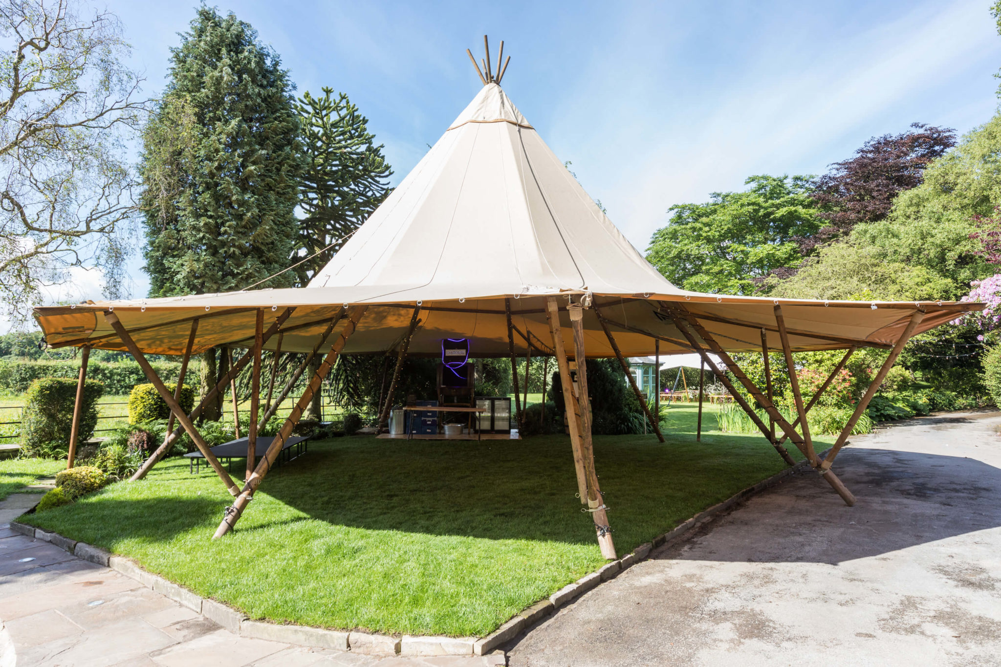 A photograph of a Tipi tent setup similar to a gazebo providing a shaded area for guests