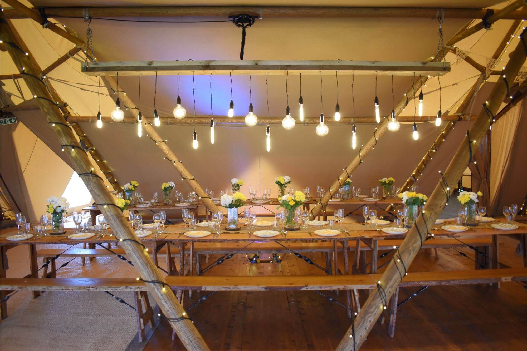 A photograph of the inside of on the the Tipi's. With beautiful lighting and benches for guests to sit on and enjoy food.
