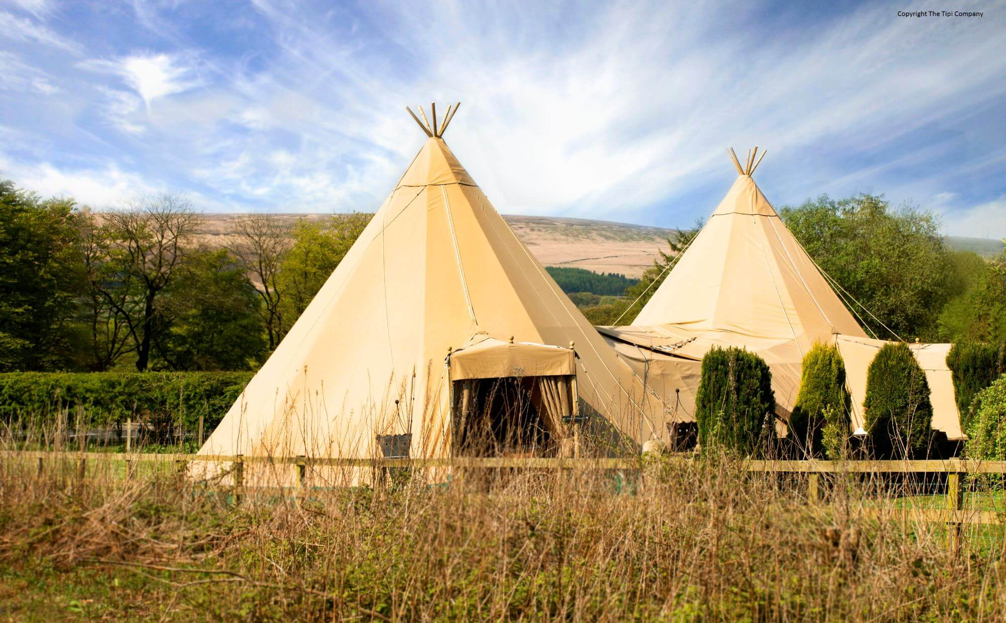 A photograph of two Tipis out in a green field