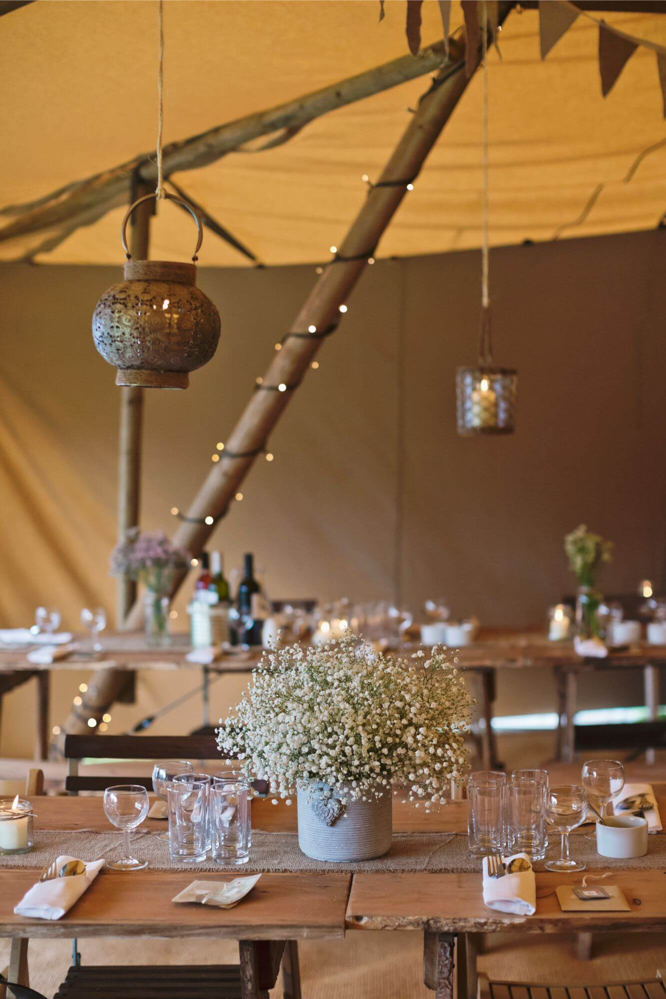 An inside photograph of the inside of a Tipi, setup with beautiful lighting, flowers and dining ware.