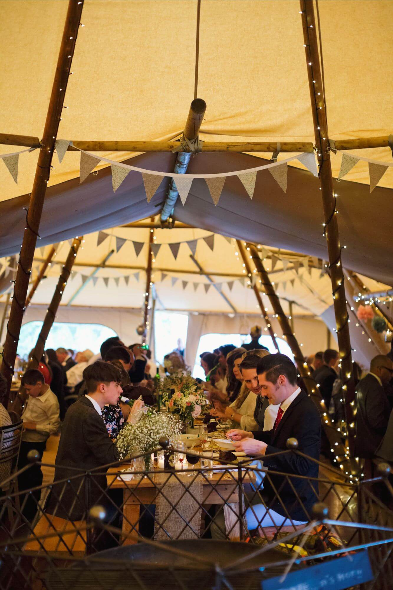 An inside photograph of the inside of a Tipi, setup with beautiful lighting, flowers and dining ware. with people enjoying food