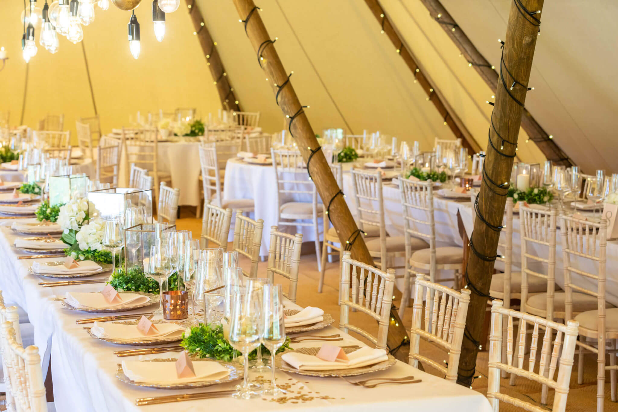 A photograph of inside a Tipi tent setup to serve dinner with fairy lights
